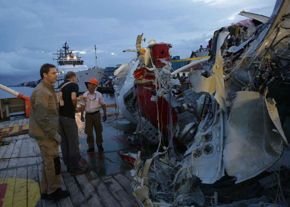 An Indonesian member of  National Transportation Safety Board talk with a foreign investigator  near part of the tail of AirAsia Flight 8501  on the deck of rescue ship Crest Onyx   at Kumai port in Pangkalan Bun,Sunday.