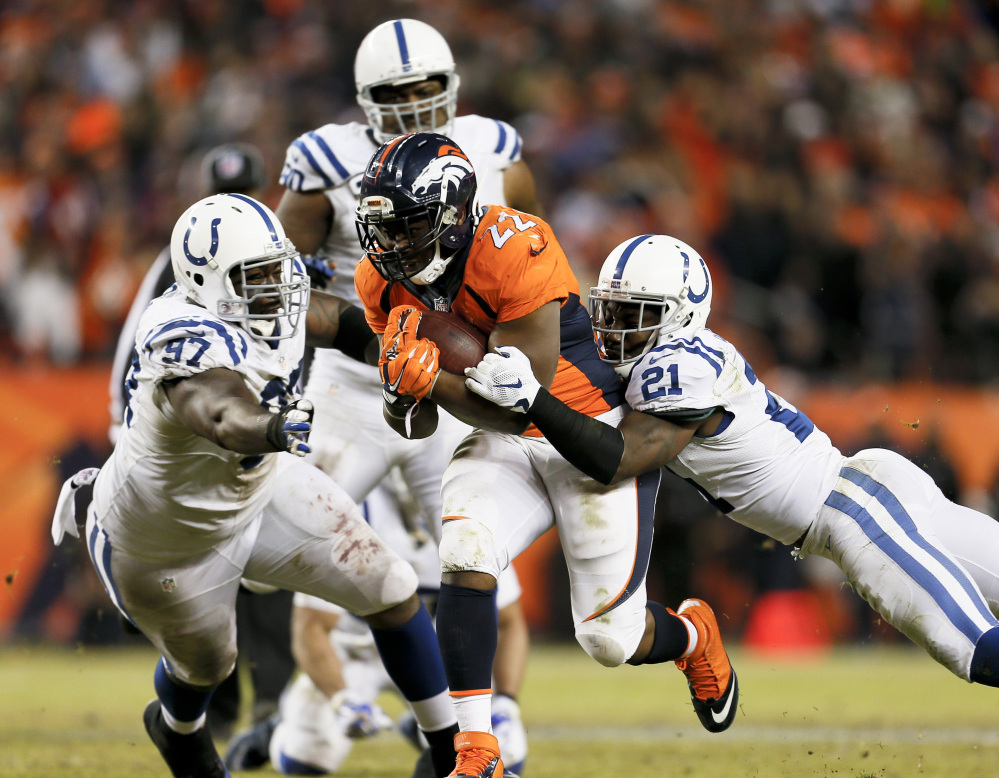 Denver Broncos running back C.J. Anderson, middle, converts a fourth down run for a first down as Indianapolis Colts cornerback Vontae Davis (21) and Arthur Jones (97) tackle him Sunday in Denver. The Associated Press