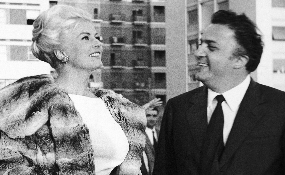 "Actress Anita Ekberg and director Federico Fellini chat near Rome. ""La Dolce Vita"" sealed Ekberg's sex goddess appeal."