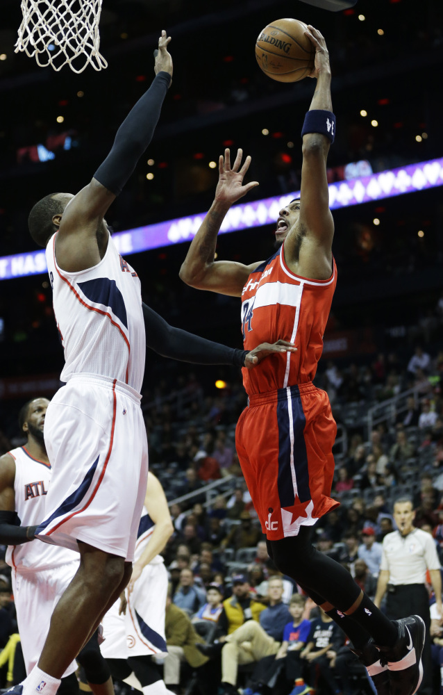 Washington's Paul Pierce takes a shot against Atlanta's Paul Millsap in the first quarter of the Hawks' 120-89 win Sunday in Atlanta.