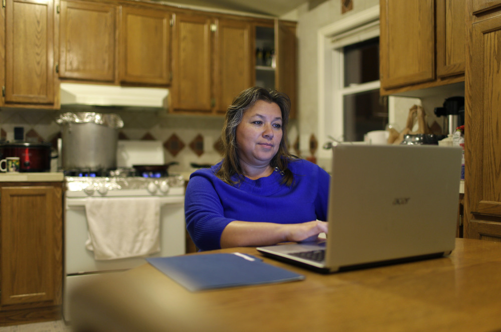 In this Dec. 2, 2014 photo, Loly Garcia works on a computer at her home in El Jebel, Colo., a small community about 20 miles northwest of Aspen, Colo. Garcia has taken lower-paying jobs in order to work closer to home.