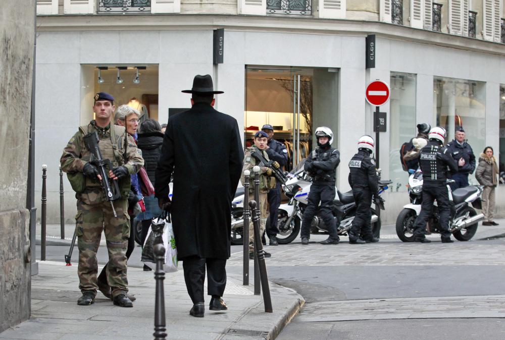 Police officers and French army soldiers patrol Rue des Rosiers in the heart of the Jewish quarter in Paris on Monday. France ordered 10,000 troops into the streets to protect sensitive sites after three days of bloodshed and terror, amid the hunt for accomplices to the attacks that left 17 people and the three gunmen dead.