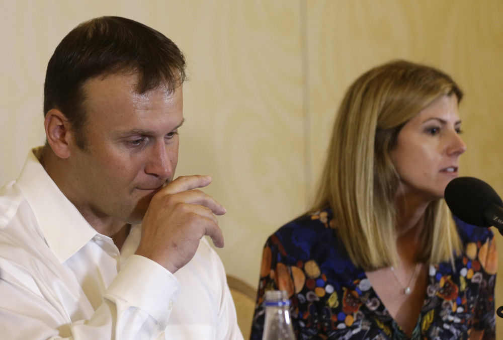 Former Miami Dolphins fullback Rod Konrad listens while his wife, Tammy, responds to a question during a news conference Monday at which he described his ordeal of swimming to shore after he fell off his boat while fishing last week off the South Florida coast.