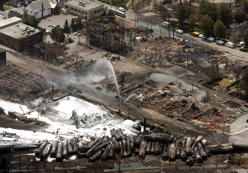 The downtown core is in ruins as firefighters water smoldering rubble in Lac-Megantic, Quebec, after a train derailed, igniting tanker cars carrying crude oil.