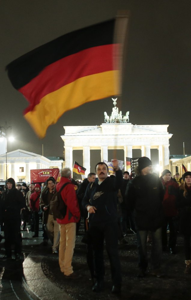 "Participants in a rally called ""Berlin Patriots against the Islamization of the West"" march in front of the Brandenburg Gate near the French embassy in Berlin on Monday."