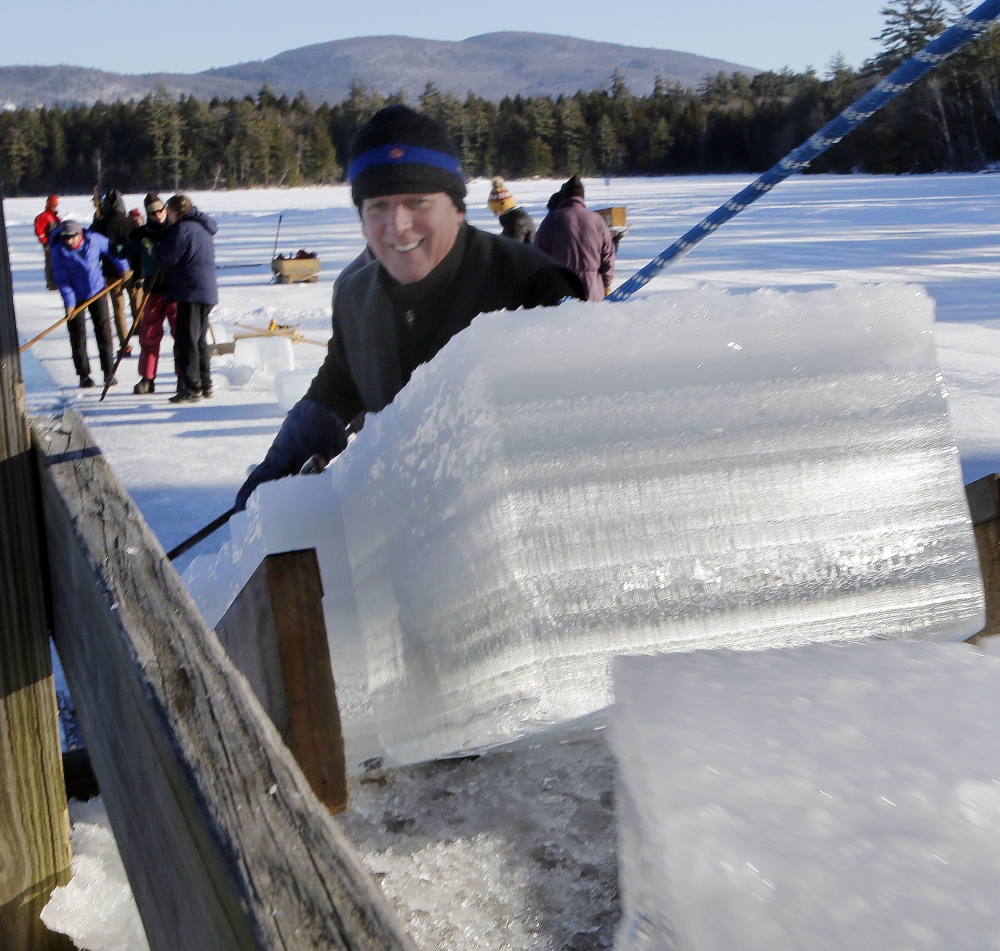 John Jurczynski loads blocks of ice, which will be stored and used in the summer at the Rockywold-Deephaven Camps instead of refrigeration units.