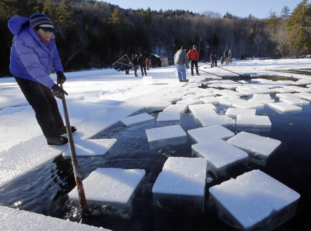 Jane Kellogg guides ice blocks weighing 120 to 160 pounds each. The annual tradition of harvesting lake ice goes back a century.