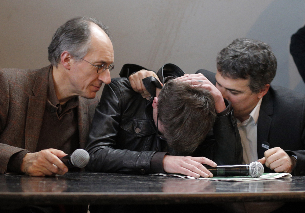 The new chief editor of French satirical magazine Charlie Hebdo, Gerard Biard, left, and columnist Patrick Pelloux, right, comfort cartoonist Luz during a press conference in Paris, France, Tuesday, Jan. 13, 2015. Twelve people died when two masked gunmen assaulted the newspaper's offices on Jan. 7, including much of the editorial staff and two police. It was the beginning of three days of terror around Paris that saw 17 people killed before the three Islamic extremist attackers were gunned down by security forces. Charlie Hebdo had faced repeated threats for depictions of the prophet, and its editor and his police bodyguard were the first to die. (AP Photo/Christophe Ena)