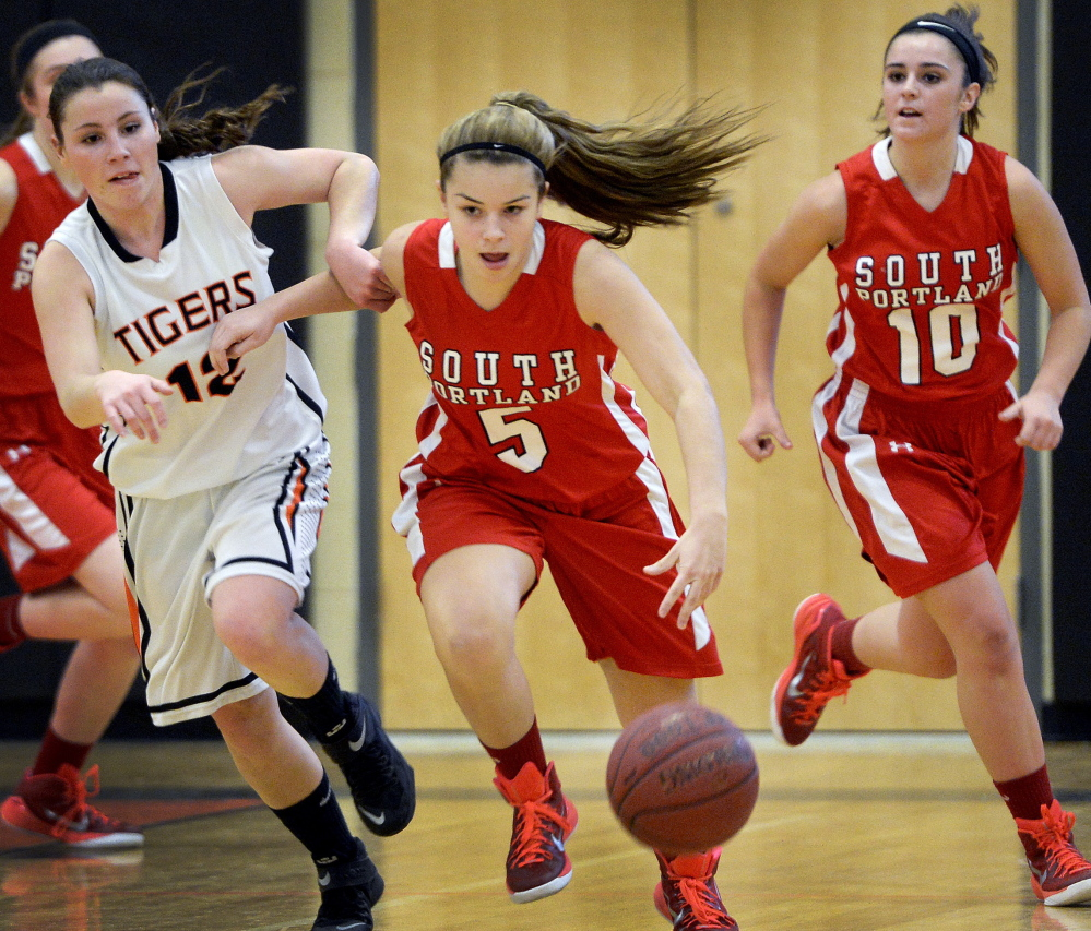 Grace Soucy of South Portland attempts to pull away from Abby Hale of Biddeford while dribbling down the court Tuesday night during South Portland's 58-35 victory in an SMAA game on the road.