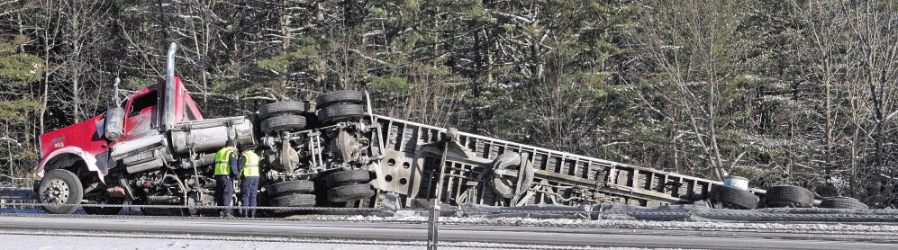 State Police troopers work the scene of a tractor trailer accident on Tuesday at Mile 111 in the northbound lane of Interstate 95 in Augusta. Traffic was backed up as it narrowed to one lane to go around the scene.
