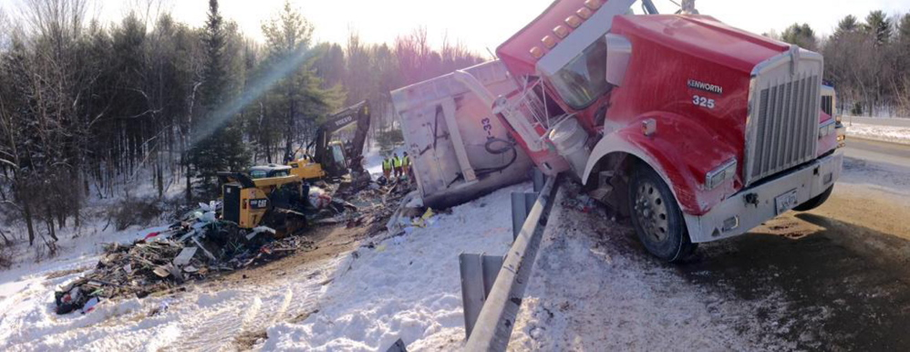 An excavator and skid loader pick up garbage Wednesday as workers prepare to remove a tractor trailer that crashed on Interstate 95 near Augusta Tuesday afternoon.