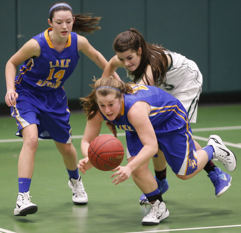 Spencer True of Lake Region dives for the basketball ahead of her teammate, Chandler True, and Elspeth Olney of Waynflete during Lake Region's 52-29 victory Wednesday in a Western Maine Conference game.