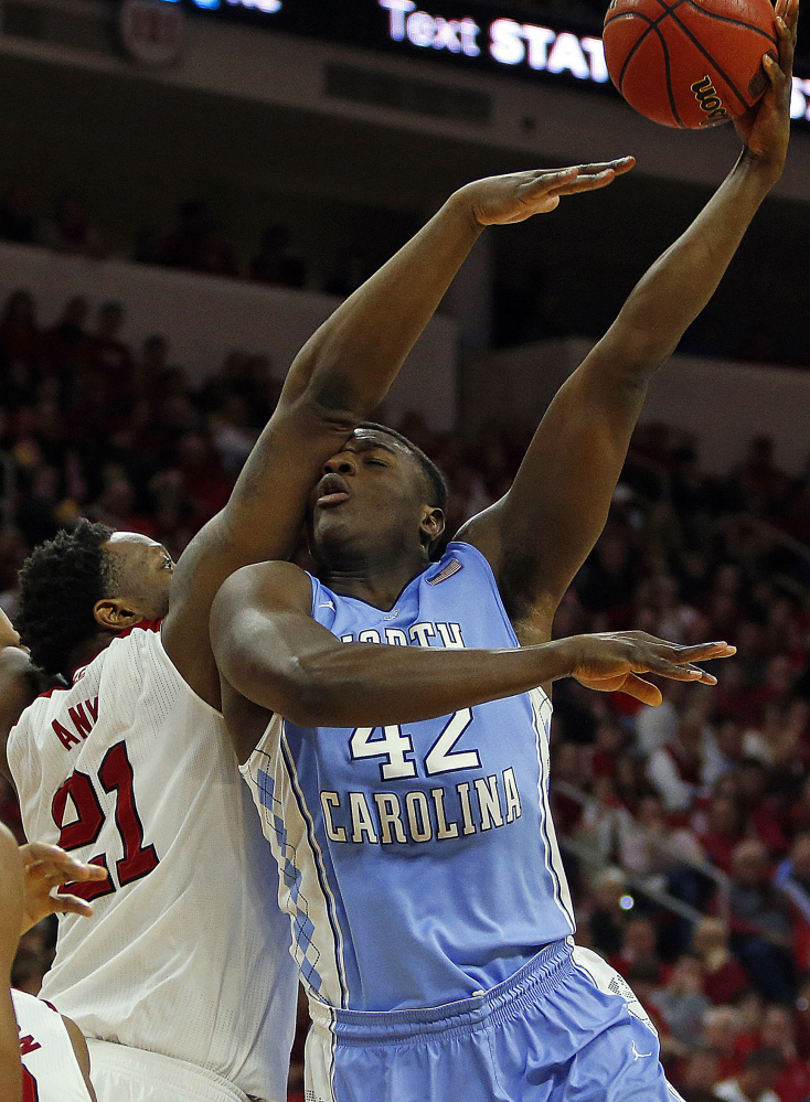 North Carolina's Joel James tries to shoot the ball over North Carolina State's Beejay Anya during the second half of Wednesday's game in Raleigh, won by the Tar Heels, 81-79.