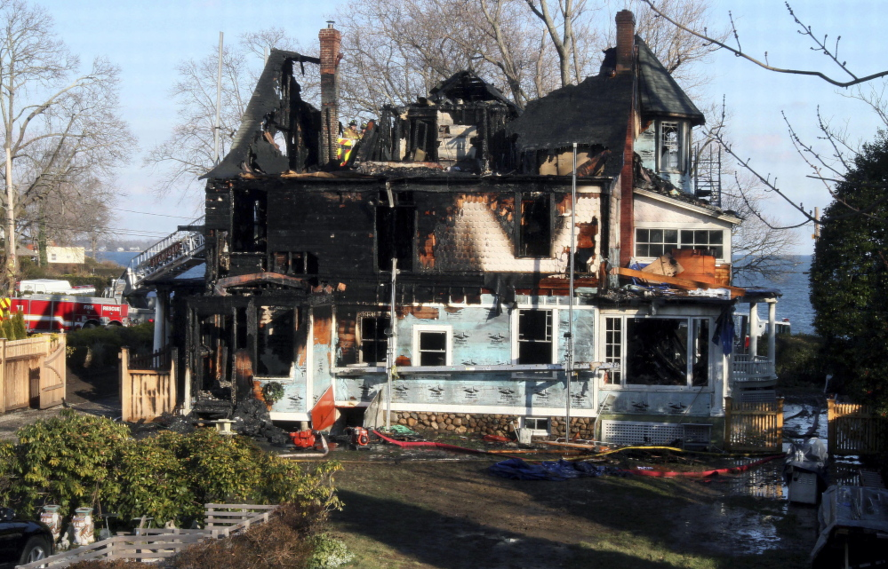 Firefighters investigate the home in Stamford, Conn., where a Christmas Day 2011 fire killed three young girls and two of their grandparents.
