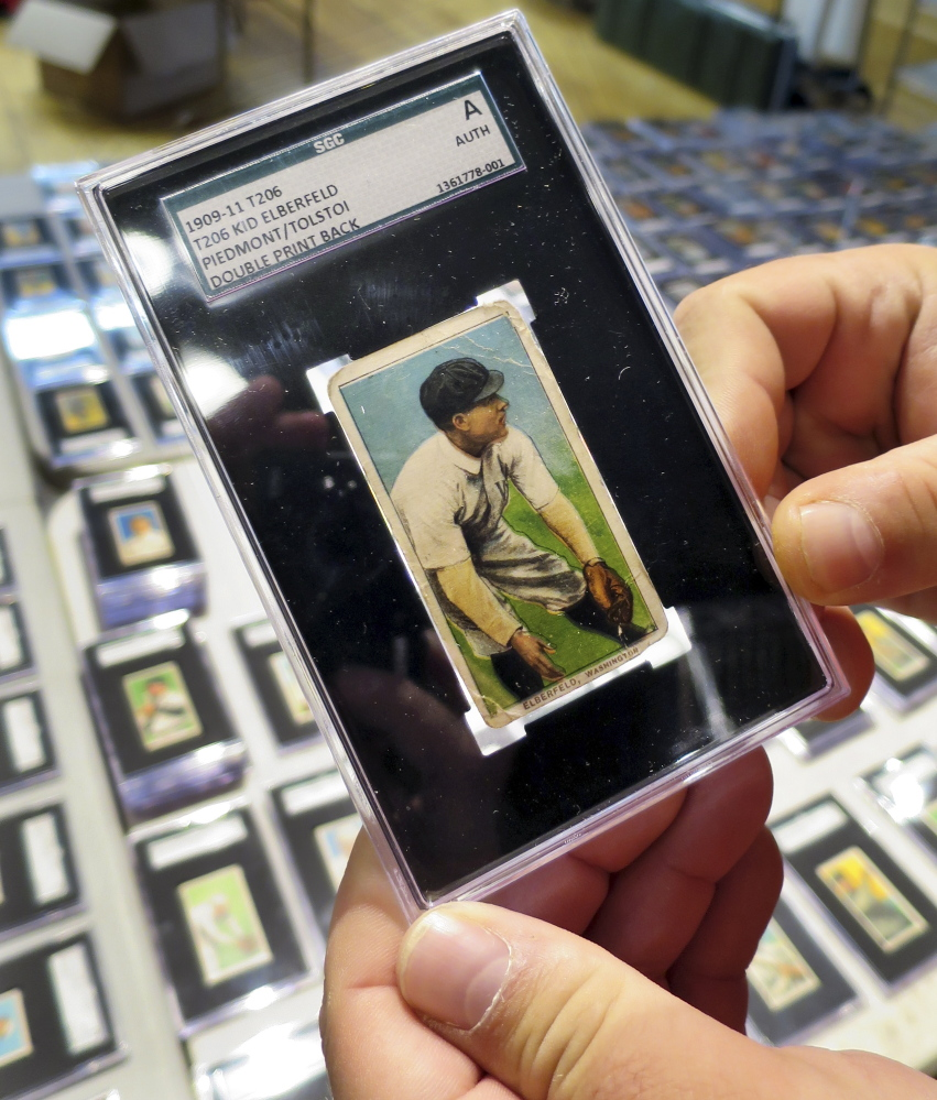 A 1909 baseball card depicting Kid Elberfeld is held by Troy Thibodeau at Saco River Auction Co. in Biddeford.