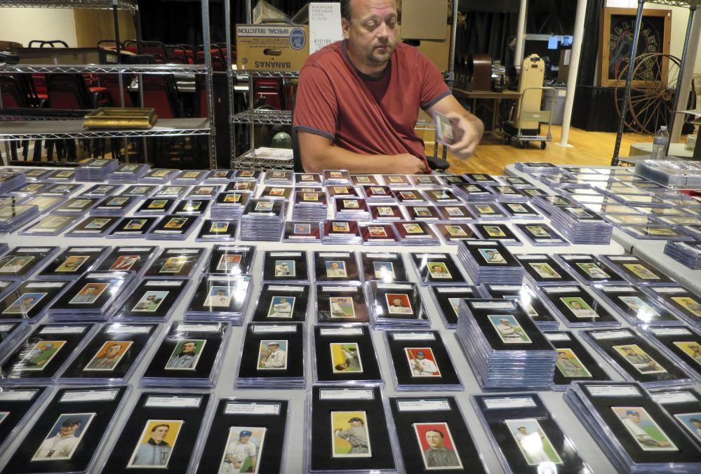 Troy Thibodeau of Saco River Auction Co. examines a collection of more than 1,400 baseball cards from 1909-1911 in Biddeford. The first batch of the collection was auctioned Wednesday night.
