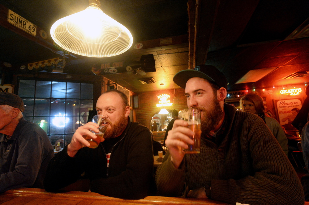 Chad Hutchins, left, and Alexander Jones of South Portland drink Foundation Epiphany IPA at the Great Lost Bear in Portland during the Industrial Park Challenge on Thursday.