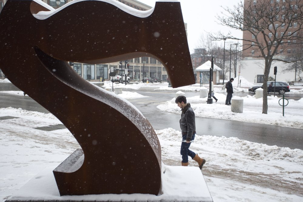 "A man walks past the ""Seven"" sculpture in front of the Portland Museum of Art on Thursday. The sculpture was vandalized last month. Gabe Souza/Staff Photographer"