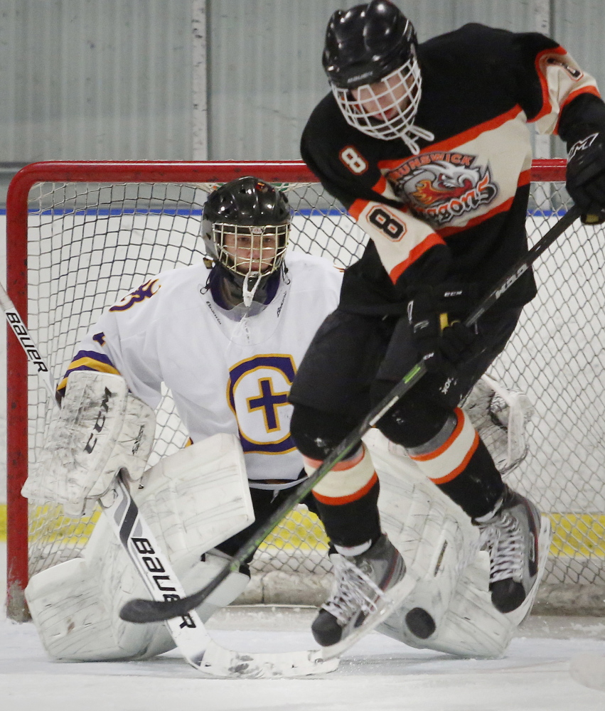 T.J. Sullivan of Brunswick leaps over a teammate's shot Thursday night as Cheverus goalie Kyle Severance keeps his eyes on the puck in the second period of Cheverus' 8-1 victory.