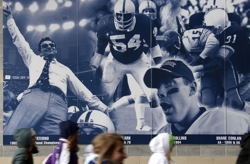 Penn State students rush into Beaver Stadium past a mural containing a photo commemorating former football coach Joe Paterno, left rear, and Penn State All-American football players. A proposed settlement would restore Penn State's 112 football wins that were vacated two years ago in the Jerry Sandusky child molestation scandal.