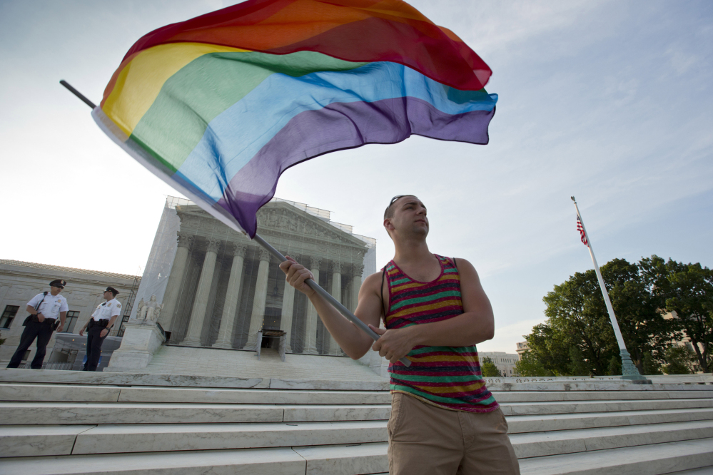 Gay rights advocate Vin Testa waves a rainbow flag in front of the Supreme Court in Washington. The justices will consider the legal debate over gay marriage in April.