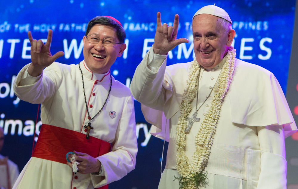 "Pope Francis and Manila Archbishop Luis Antonio Tagle salute the crowd with the popular hand sign for ""I love you"" during a meeting with families at the Mall of Asia arena in Manila, Philippines, on Friday."