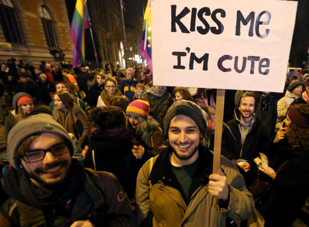 A crowd in Vienna, Austria, holds flags and signs Friday during a protest in front of a cafe where a lesbian couple was asked to leave because they were kissing.