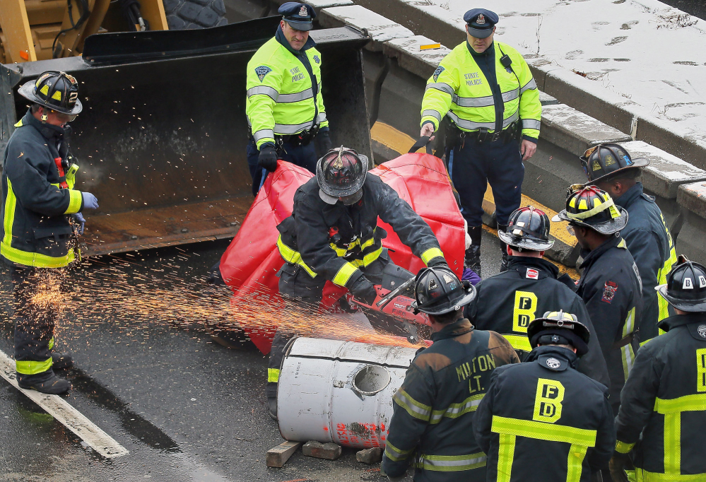 "Firefighters use a saw to cut away a barrel that protesters locked themselves to in order to block the morning commute Thursday in Milton, Mass. Activists were protesting what they called ""police and state violence against black people."""