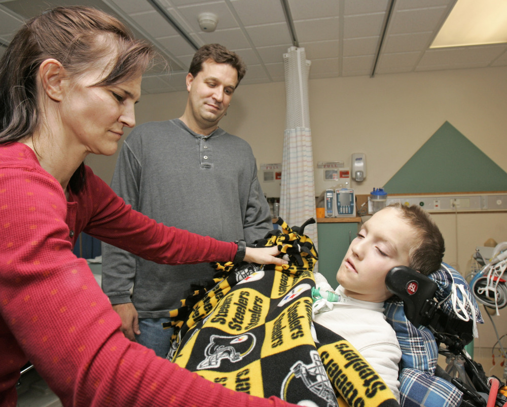 Beth Malarkey covers up her son, Alex, with a blanket as Alex's father, Kevin, watches at University Hospital's Case Western Reserve Medical Center in Cleveland in 2009. Alex Malarkey was in a 2004 car crash that left him paralyzed below the neck.