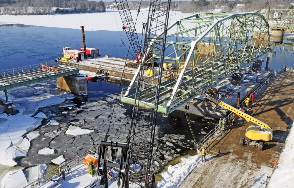Reed and Reed Construction workers dismantle a section of the old Richmond-Dresden Bridge on Friday on a barge on the Dresden shore of the Kennebec River.