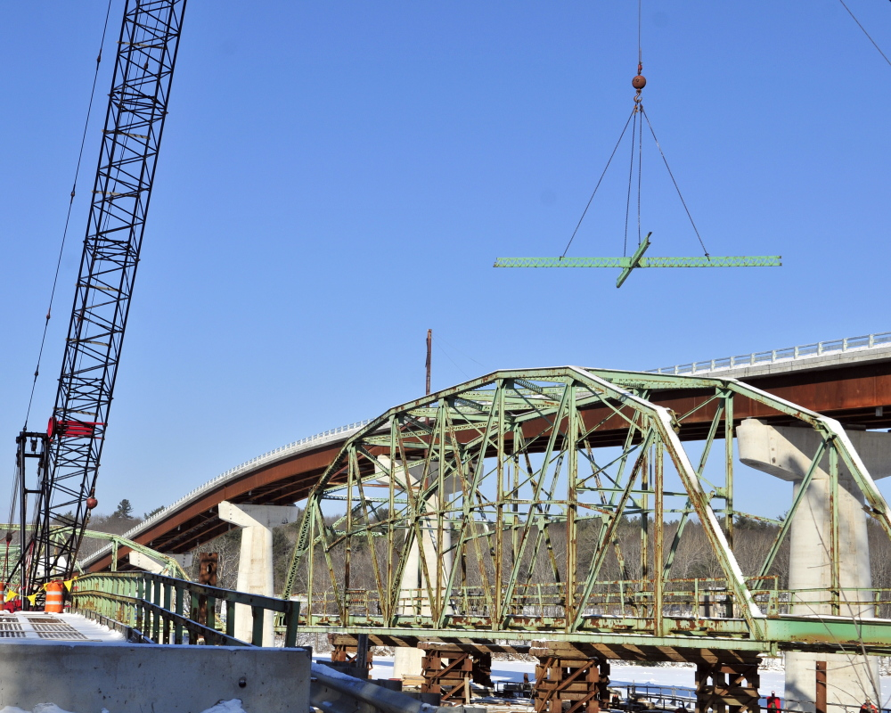 A Reed and Reed Construction crane lifts a section of beams that were just cut out as workers dismantle the old Richmond-Dresden Bridge on Friday on a barge on the Dresden shore of the Kennebec River.