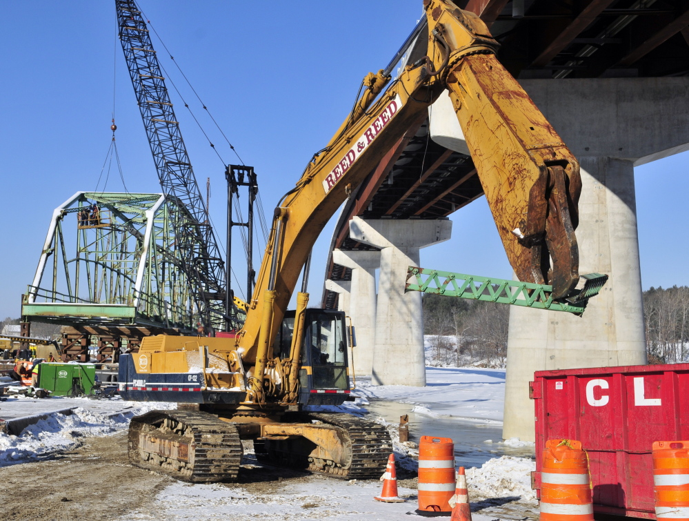 An excavator carries a piece of beam into a large container as workers dismantle the old Richmond-Dresden Bridge on Friday on a barge on the Dresden shore of the Kennebec River.