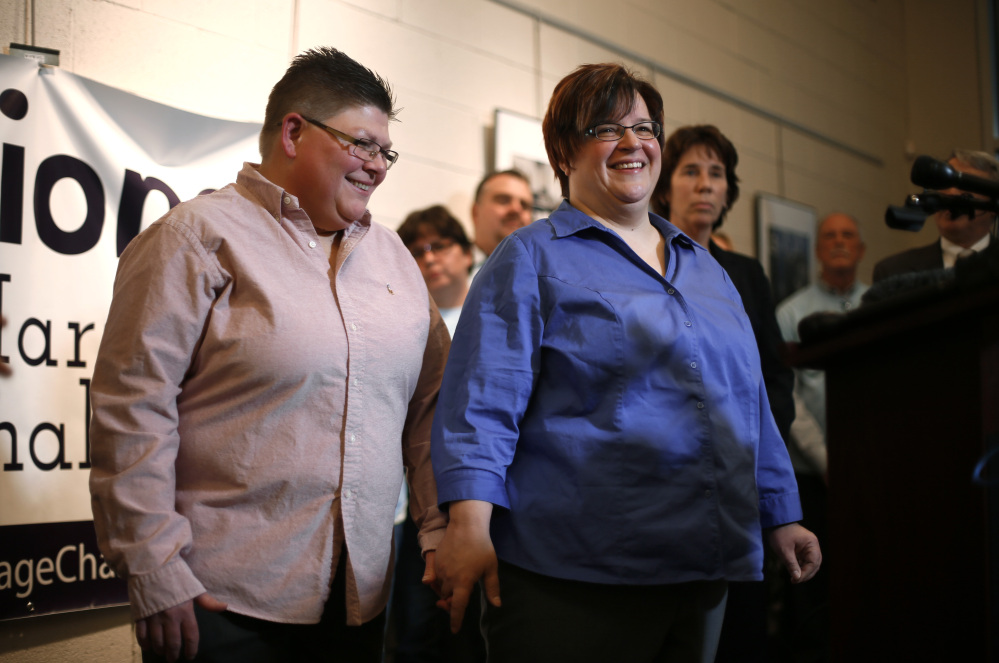 Jayne Rowse, left, and partner April DeBoer, of Hazel Park, Mich., smile during a news conference, Friday, Jan. 16, 2015, in Ferndale, Mich. Setting the stage for a potentially historic ruling, the Supreme Court says it will decide whether same-sex couples nationwide have a right to marry under the Constitution. The justices said Friday they will review an appellate ruling that upheld bans on same-sex unions in four states. Kentucky, Michigan, Ohio and Tennessee are among the 14 states where gay and lesbian couples are not allowed to marry. (AP Photo/Paul Sancya)