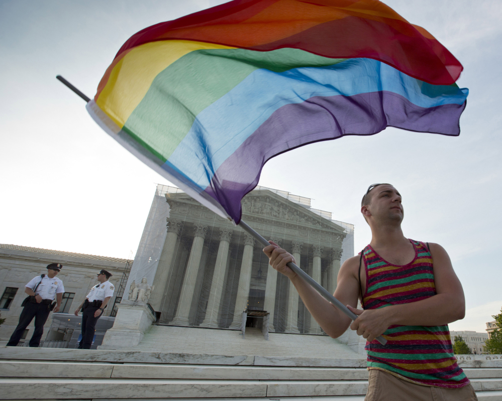 A gay rights advocate waves a rainbow flag in front of the Supreme Court in Washington. Justices will decide in April whether same-sex marriage is a constitutional right.