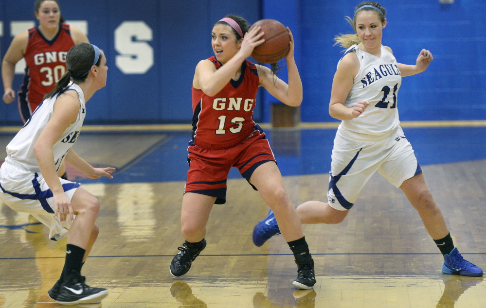 Alicia Dumont of Gray-New Gloucester looks for a teammate Friday night while guarded by Mackenzie Rague, left, and Abby Dubois of Old Orchard Beach during Gray-New Gloucester's 52-40 victory on the road.