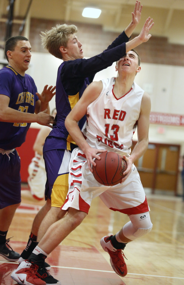South Portland's Jack Fiorini looks for an opening Friday against Austin Boudreau, center, and Zordan Holman of Cheverus. Fiorini scored 18 points in a 61-50 win.