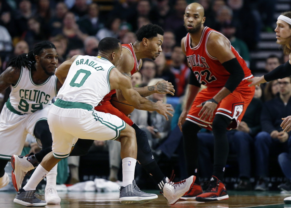 Derrick Rose of the Chicago Bulls loses control of the ball Friday night while driving past Avery Bradley, center, and Jae Crowder of the Boston Celtics in the first period of the Bulls' 119-103 victory at Boston.
