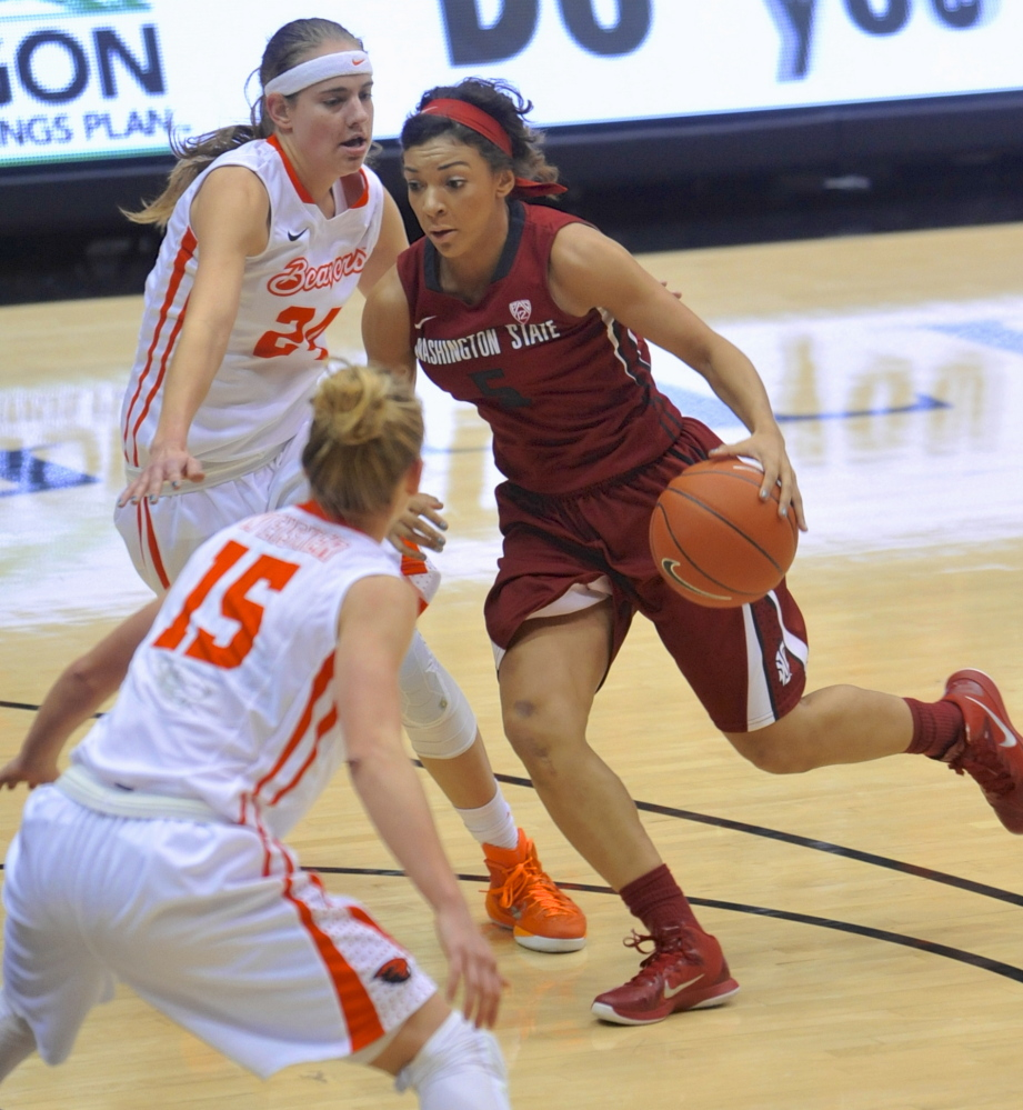 Tia Presley of Washington State drives against Oregon State's Sydney Wiese, top, and Jamie Weisner during the first half of their Pac-12 game Friday in Corvallis, Ore. Ninth-ranked Oregon State won, 73-70.