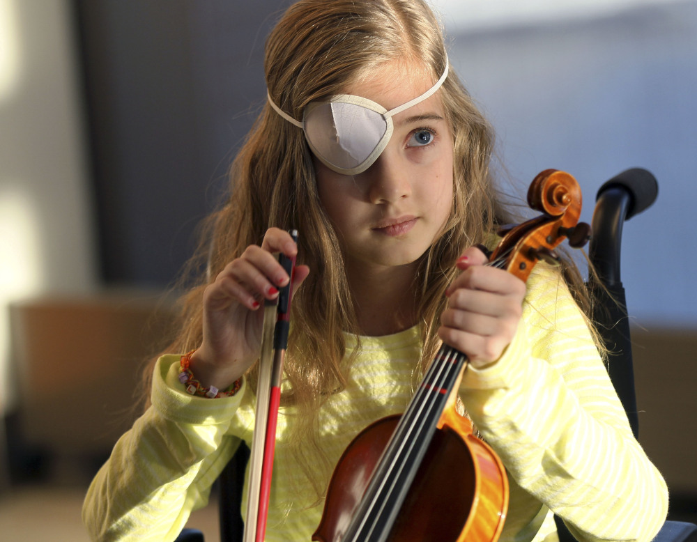 Sophie Fellows, 9, of Colchester, Vt., who is recovering from brain surgery, picks up her violin at Spaulding Rehabilitation Hospital in Boston. With the help of a music therapist, Sophie is learning to play her violin again.