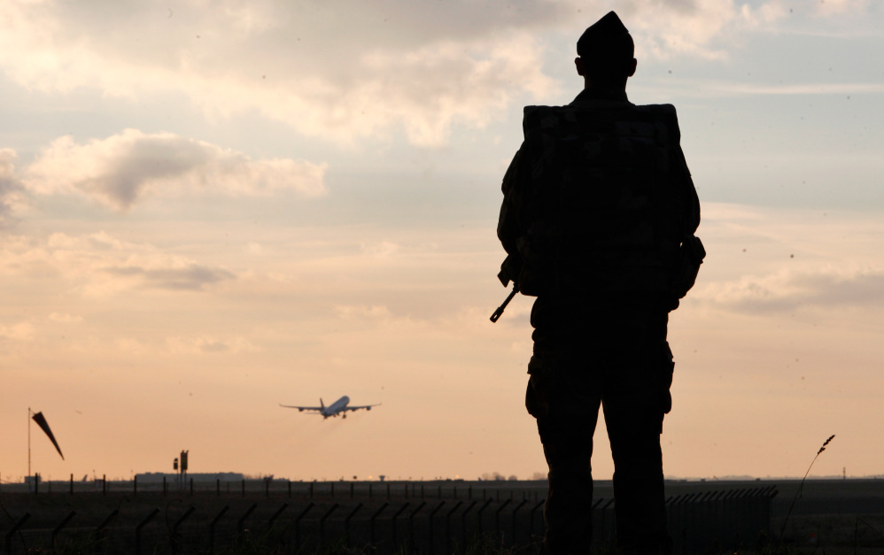 A plane takes off as a French soldier patrols at Paris Roissy Charles de Gaulle airport, in Roissy, north of Paris, on Saturday. Since last week's attacks on a the offices of a satirical magazine, France has bolstered police presence in the streets and at sensitive sites.
