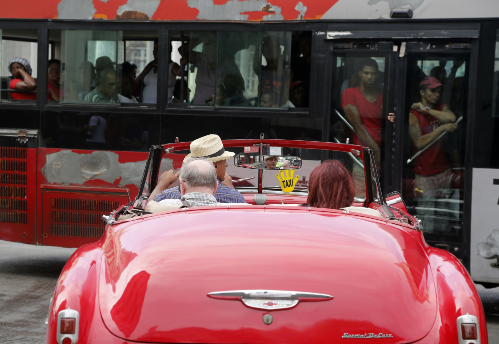 Commuters ride a public bus as tourists set off for a spin in a classic American convertible in Havana, Cuba. Tens of thousands more American tourists are expected to flock this year to a country where some five-star hotels don't have working air-conditioning or hand towels. The Associated Press