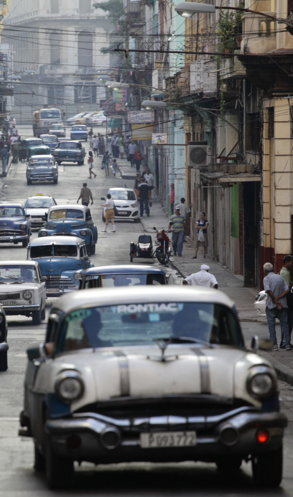 Classic American cars used as collective taxis drive along a street in Havana on Friday. The number of Americans traveling to Cuba is expected to double this year.