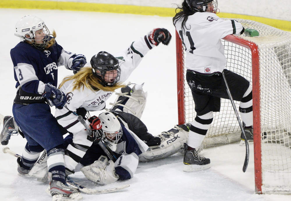 Hannah Bosworth of Cape Elizabeth/Waynflete celebrates Saturday, falling to the ice after her teammate, Kathryn Clark, right, scored during a 6-1 loss to Yarmouth/Freeport. Defending are Jenny Holmquist and goalie Hannah Williams.