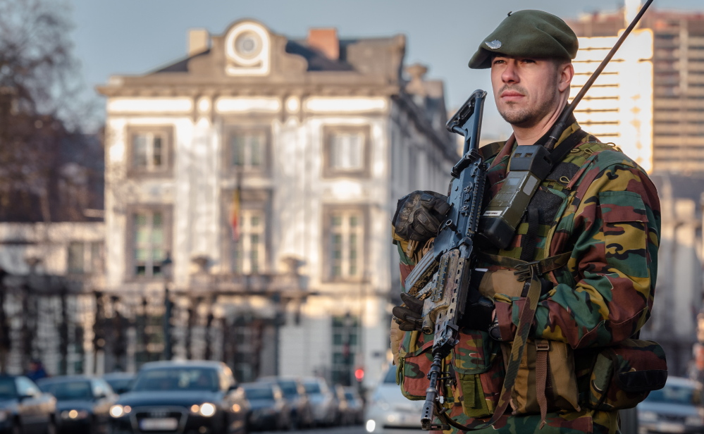 A Belgian para-commando patrols near the office of the prime minister in Brussels on Saturday. Security around Belgium has been stepped up since 13 people were detained.