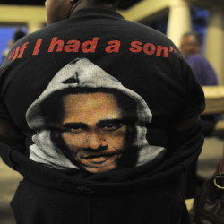 "A woman wears a T-shirt with a rendering of President Obama in a hoodie before a candlelight vigil for Trayvon Martin in Sanford, Florida, in 2013. The shirt refers to Obama's reaction to the death of the unarmed black teenager: ""You know, when Trayvon Martin was first shot, I said that this could have been my son,"" he said. ""Another way of saying that is Trayvon Martin could have been me 35 years ago."""