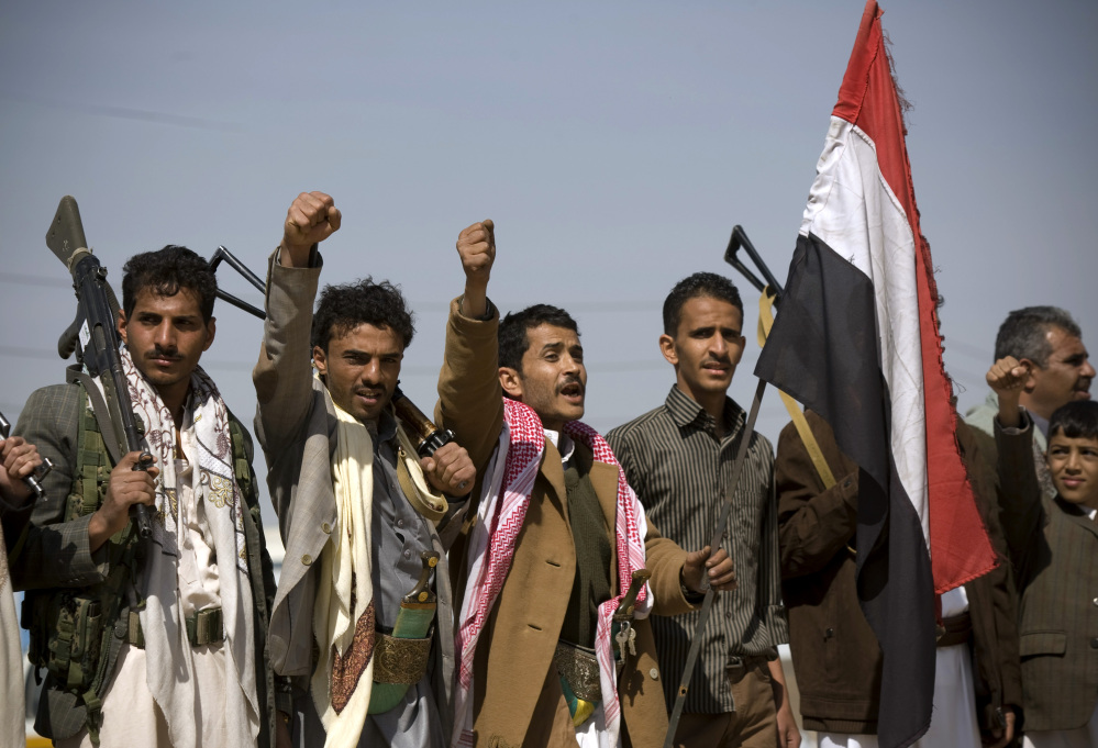 Houthi Shiite Yemenis raise their fists during clashes near the presidential palace in Sanaa, Yemen, Monday.