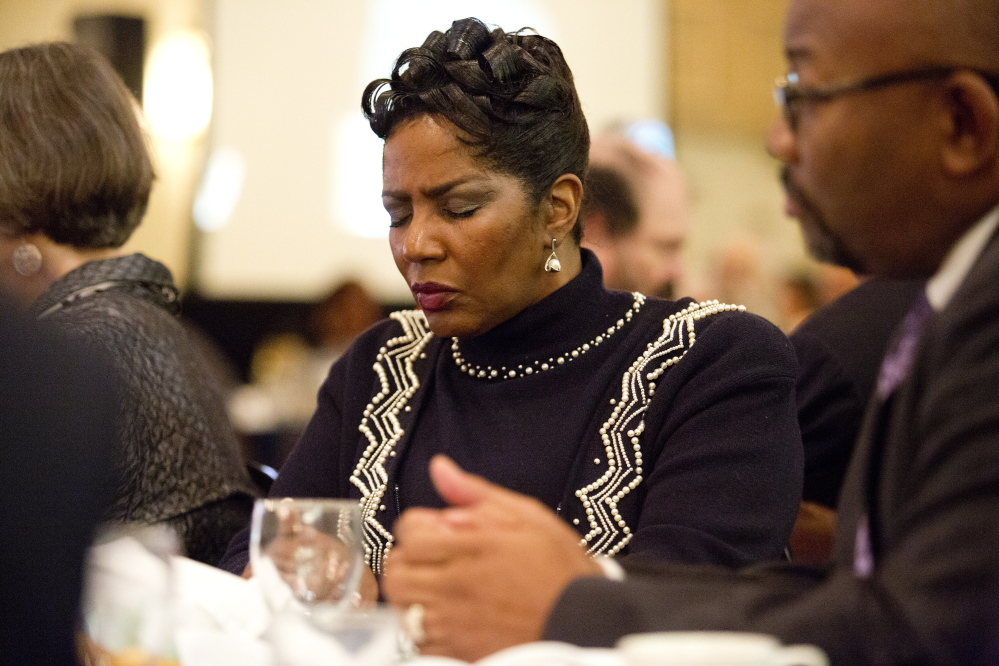 Patricia Malone of Falmouth prays during the annual MLK Jr. Day breakfast hosted by the NAACP at the Holiday Inn by the Bay on Monday in Portland.