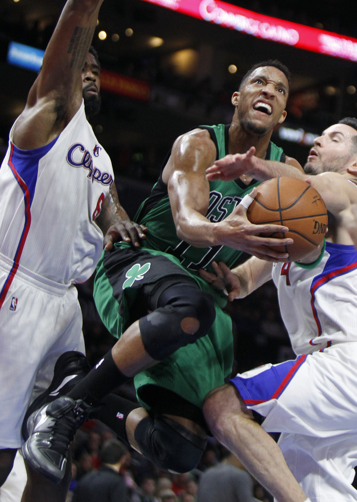 Celtics guard Evan Turner splits the defense of  Los Angeles Clippers DeAndre Jordan, left, and guard J.J. Redick to take a shot during the first half of Monday's game in Los Angeles