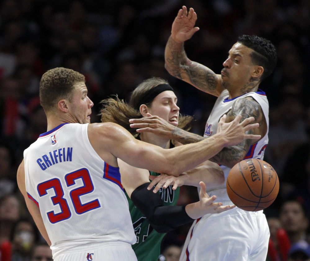 Boston Celtics center Kelly Olynyk makes a pass by Los Angeles Clippers forward Blake Griffin (32) and forward Matt Barnes during the second half of Monday's game in Los Angeles. The Clippers won, 102-93.