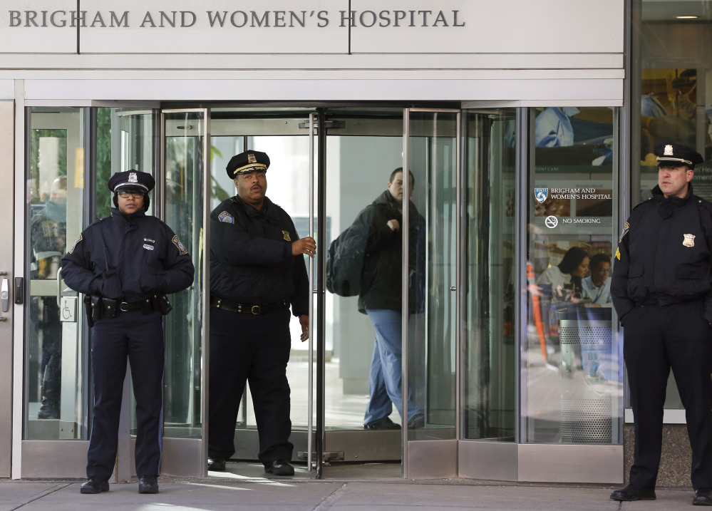 Boston police Superintendent-in-Chief William Gross, center left, walks through a revolving door as he leaves the Shapiro building at Brigham and Women's Hospital on Tuesday in Boston.